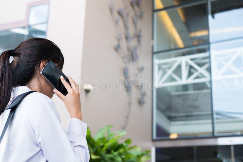 Affärskvinnasamtal på mobiltelefonen Kvinnan går till kontoret Den kvinnliga vuxna människan går framme av byggnad royaltyfri foto