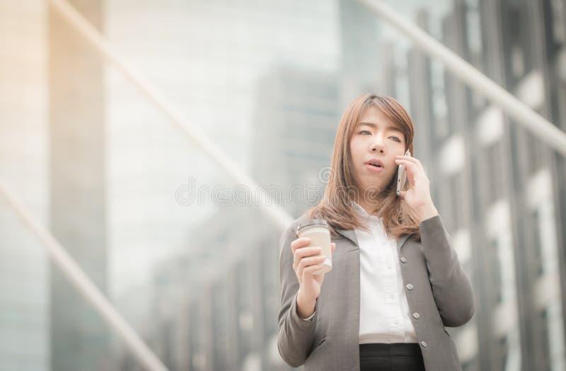 Affärskvinnasamtal till mobiltelefonen royaltyfri bild