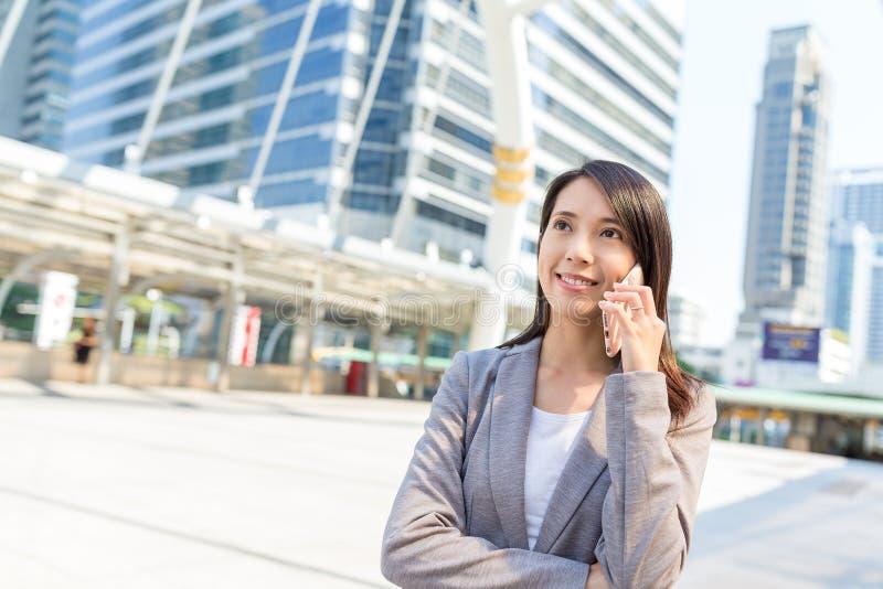 Affärskvinnasamtal till mobiltelefonen royaltyfri foto