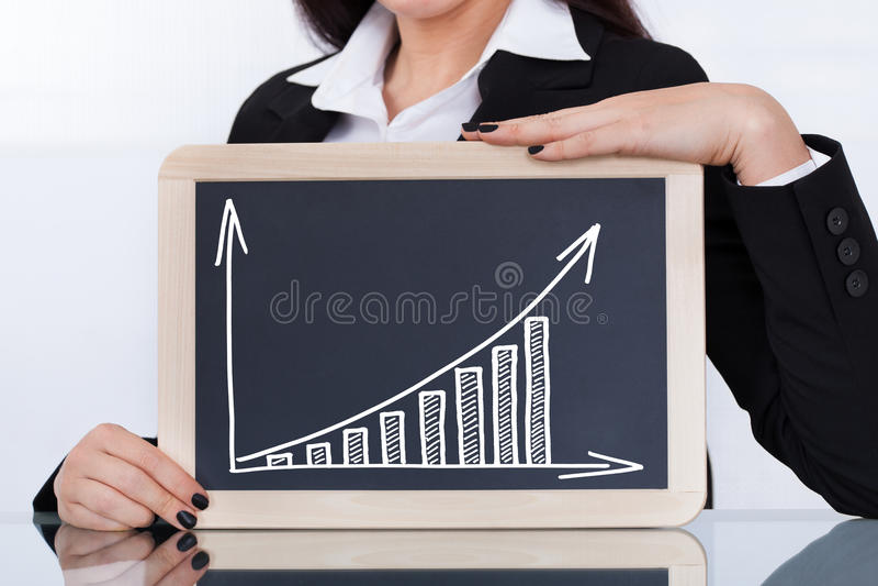 AffärskvinnaShowing Chalkboard With diagram arkivbild