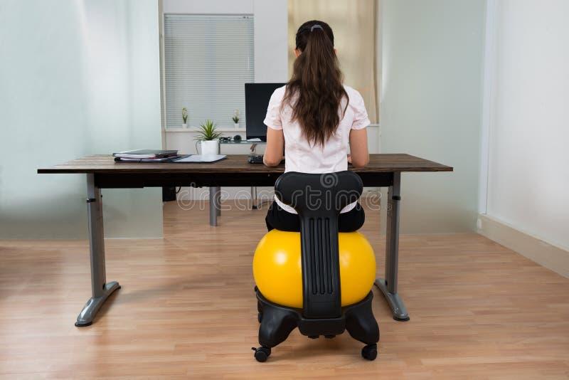 AffärskvinnaSitting On Fitness boll i regeringsställning royaltyfria bilder
