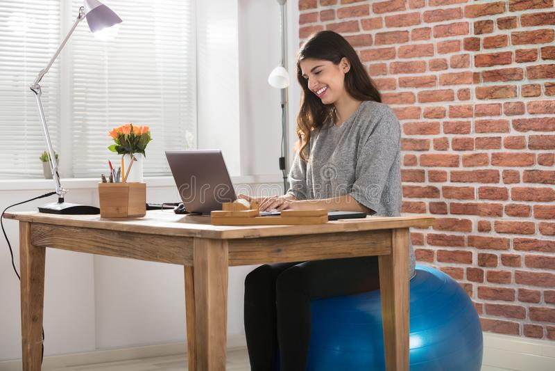 AffärskvinnaSitting On Fitness boll som i regeringsställning arbetar arkivbild