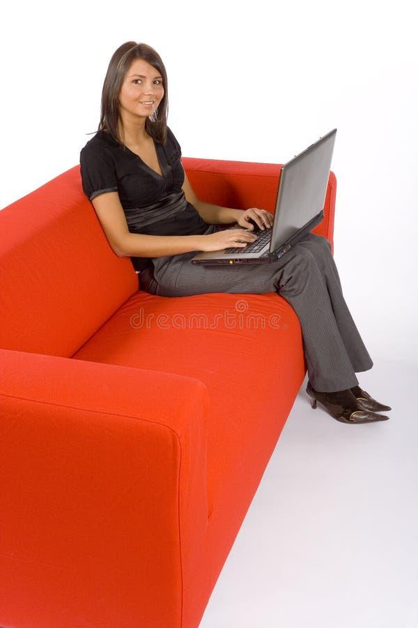affärskvinnasoffabärbar dator fotografering för bildbyråer