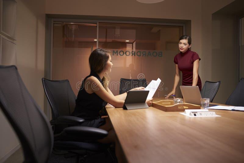 Affärskvinnaställningar som talar till kollegan som sent arbetar arkivbild