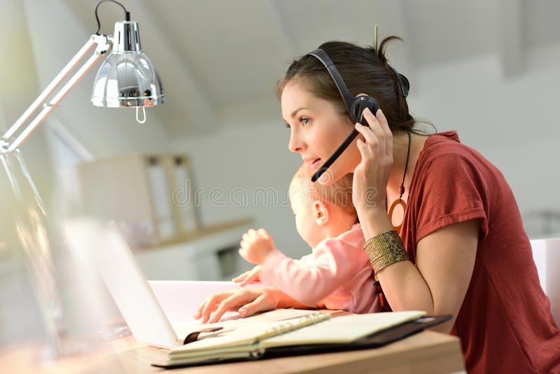 Affärskvinnateleworking på bärbara datorn som rymmer henne, behandla som ett barn arkivbilder