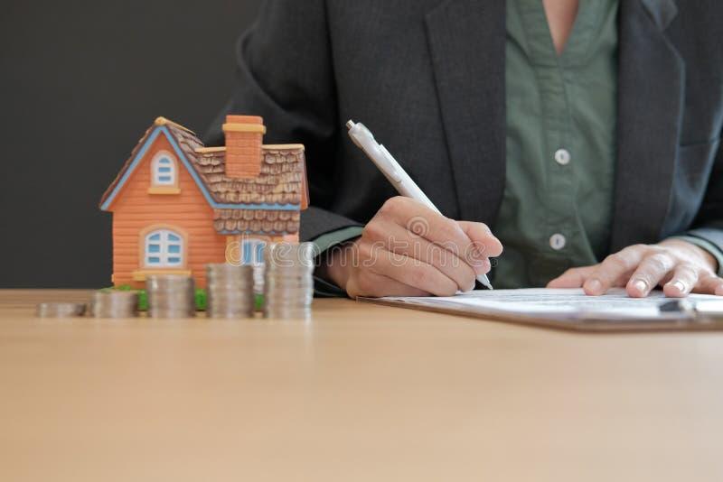 affärskvinnaunderteckning intecknar lånavtalet med husmodellen Co arkivfoto