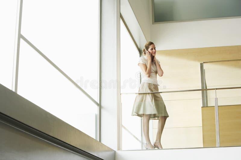 AffärskvinnaUsing Cellphone While anseende vid den Glass räcket arkivfoto