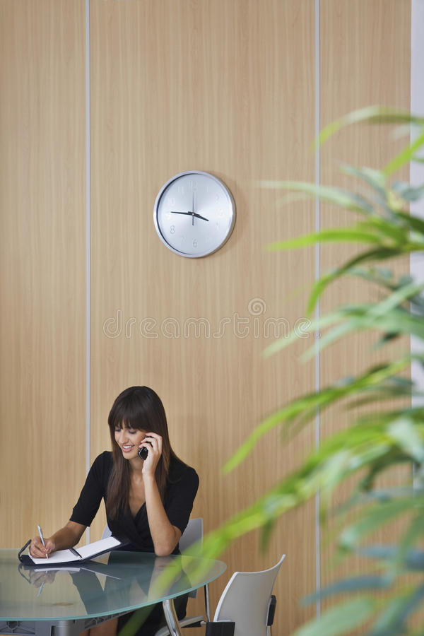 AffärskvinnaUsing Cellphone In kontor royaltyfria bilder