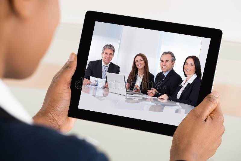 AffärskvinnaVideo Conferencing On Digital minnestavla royaltyfria bilder