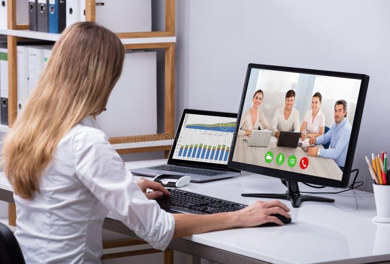 Affärskvinnavideoconferencing på datoren arkivbild