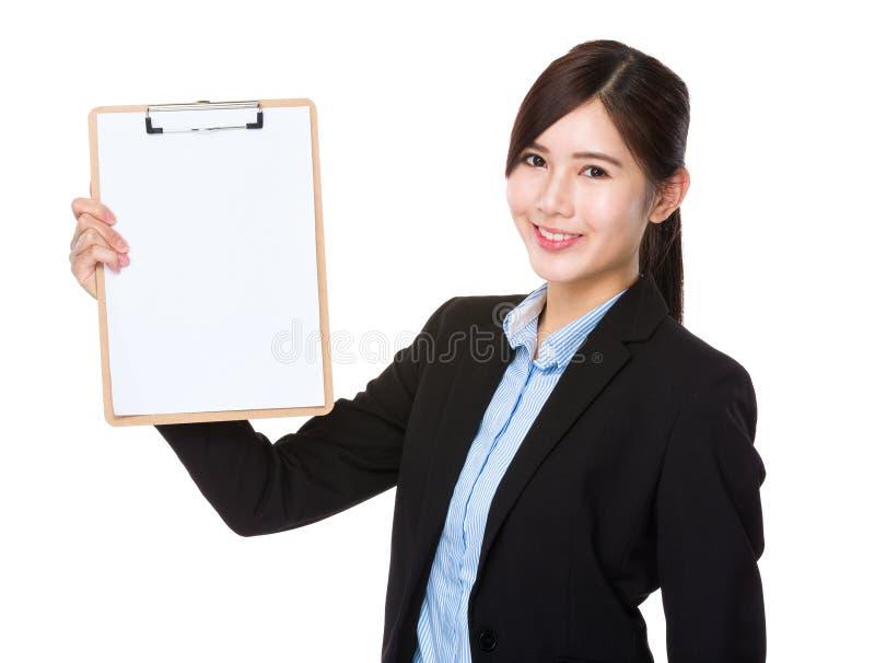 Affärskvinnavisning med den tomma sidan av skrivplattan royaltyfria bilder