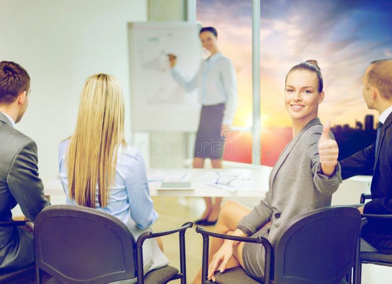 Affärskvinnavisningtummar upp på kontoret royaltyfria foton