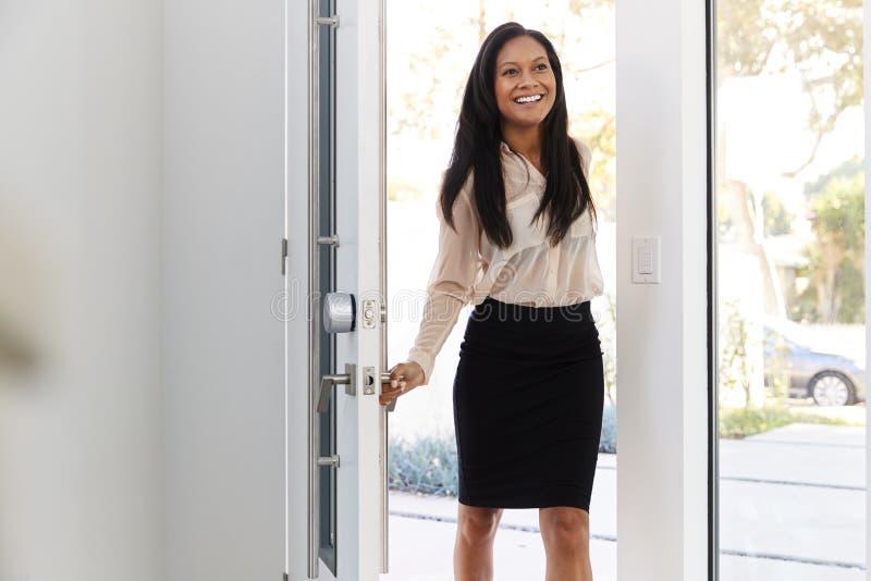 AffärskvinnaWearing Suit Opening dörr som hem går tillbaka från arbete royaltyfri foto