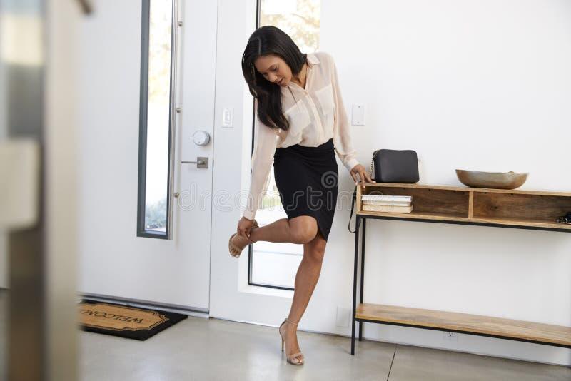 AffärskvinnaWearing Suit Returning hem från arbete och att ta av skor royaltyfria foton