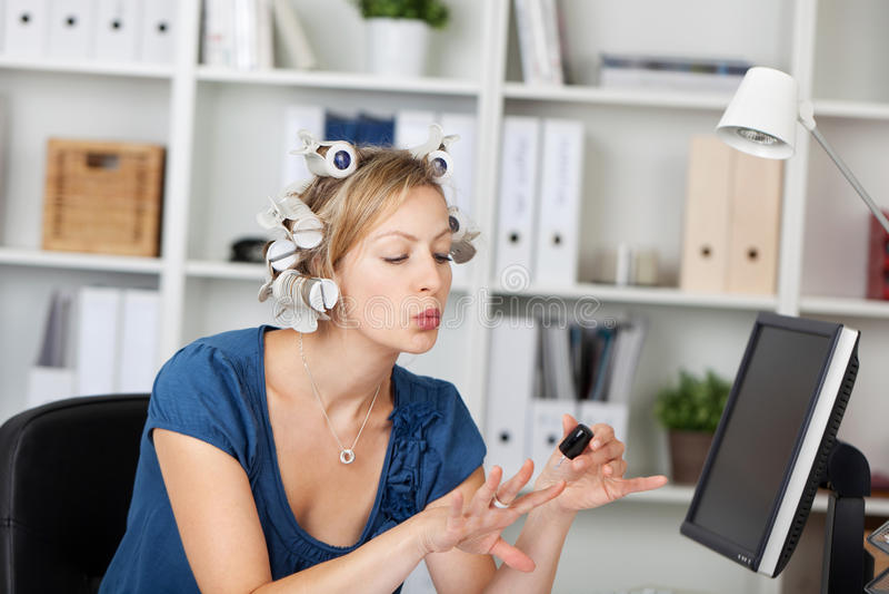 AffärskvinnaWith Curlers In hår som applicerar Nailpaint royaltyfria bilder