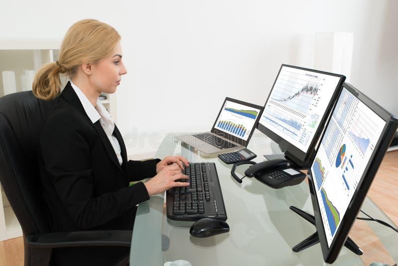 AffärskvinnaWorking With Statistics data på datoren arkivfoto
