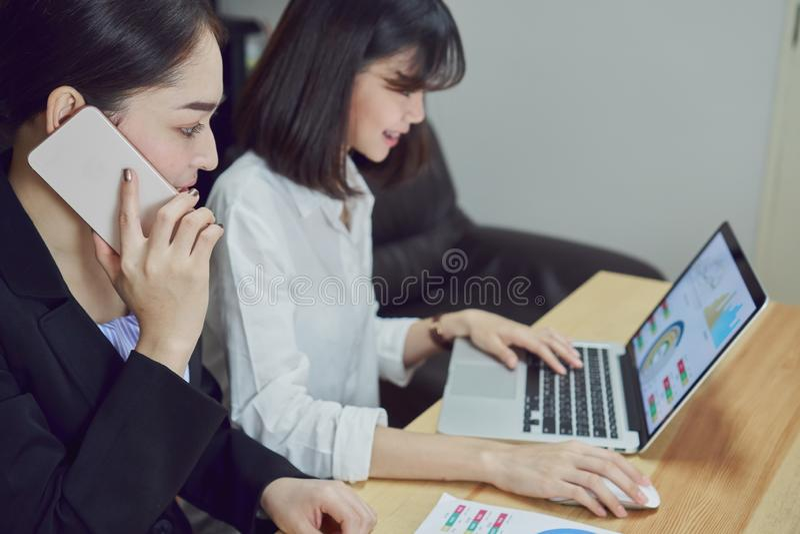 Affärskvinnor använder bärbara datorer och smartphones för att arbeta i kontoret arkivbild