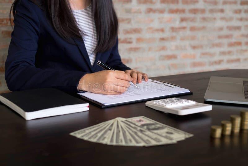 Affärskvinnor beräknar kostnaden varje dag för att hålla pengarna fena arkivfoton