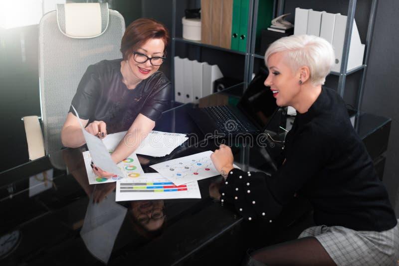 Affärskvinnor diskuterar diagram på skrivbordet i regeringsställning arkivfoton