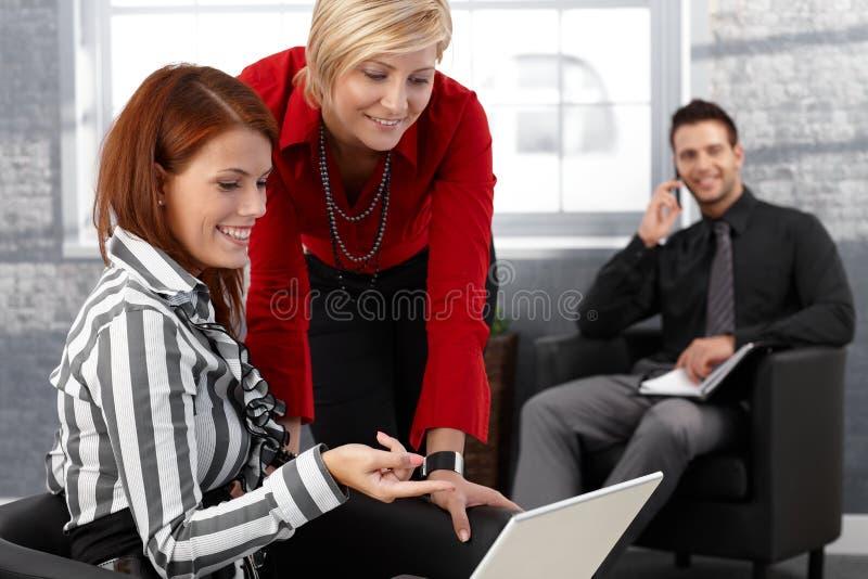 Affärskvinnor genom att använda bärbar datordatoren arkivfoto