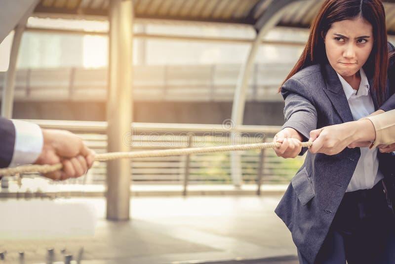 Affärskvinnor hjälper att dra repet mot affärsmannen Conc royaltyfri foto