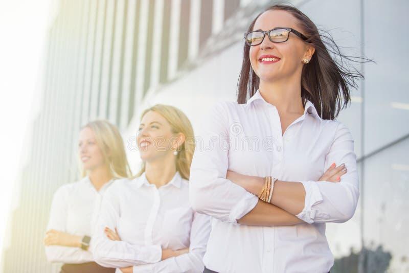 Affärskvinnor med exponeringsglas som står och ler arkivbild