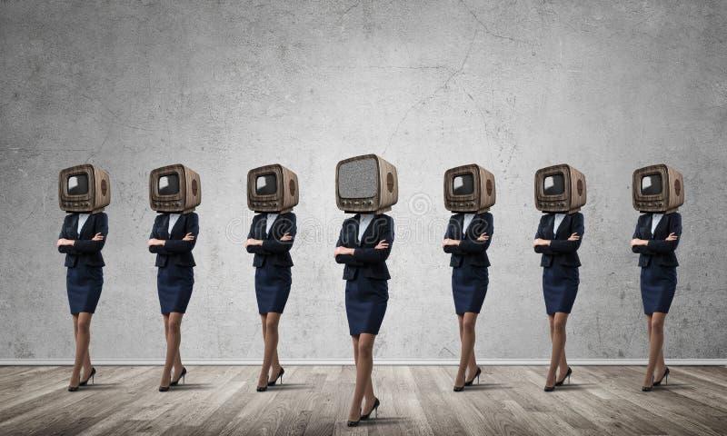 Affärskvinnor med gammal TV i stället för huvudet arkivbild