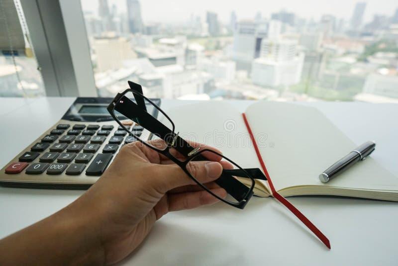 Affärskvinnor med glasögon som arbetar på budget och skatt med räknemaskinen arkivfoto