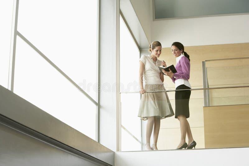 Affärskvinnor med organisatören Planning Agenda Together vid exponeringsglas R royaltyfri bild