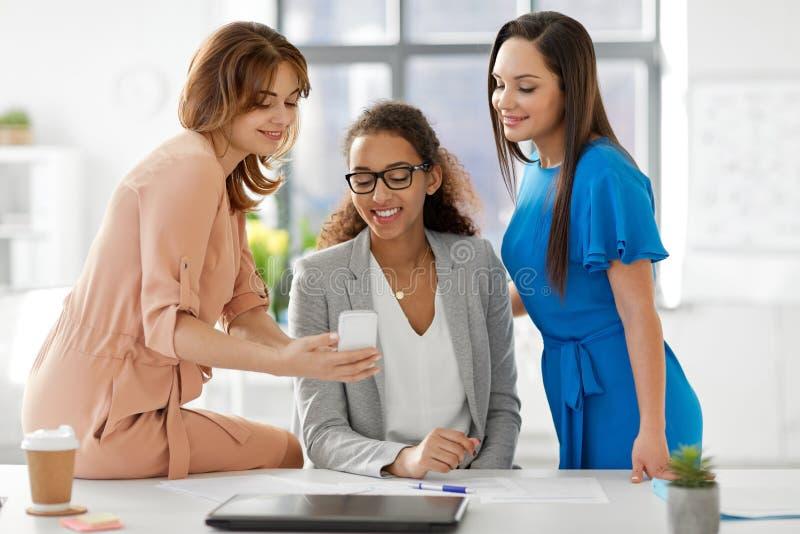 Affärskvinnor med smartphonen som arbetar på kontoret arkivfoto
