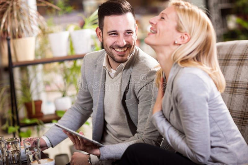 Affärskvinnor och män på ett avbrott i ett kafé, skratta och en talkin royaltyfria foton