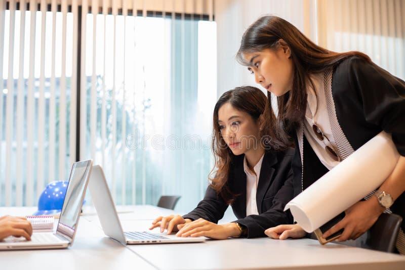 Affärskvinnor och teknikergrupp som använder anteckningsboken för affärspartners som diskuterar dokument och idéer på möte och af arkivfoto