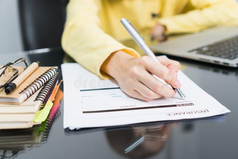 Affärskvinnor skriver försäkringdetaljer i form av försäkring royaltyfria foton
