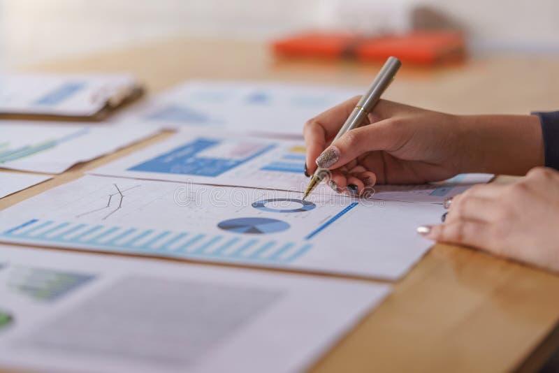 Affärskvinnor som analyserar finansiella rapporter för data på trätabellen royaltyfria foton