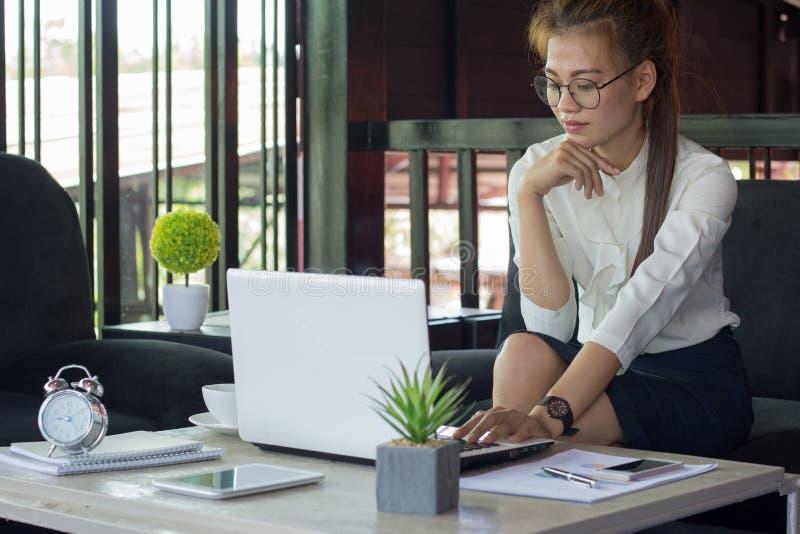 Affärskvinnor som arbetar på kontoret med bärbara datorn och dokument på högt royaltyfri bild