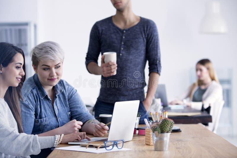 Affärskvinnor som arbetar tillsammans genom att använda bärbara datorn royaltyfri bild