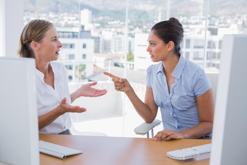 Affärskvinnor som argumenterar på deras skrivbord royaltyfri bild