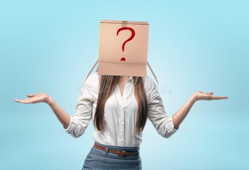 Affärskvinnor som bär lådan, boxas på hennes huvud med den utdragna röda frågefläcken royaltyfri bild