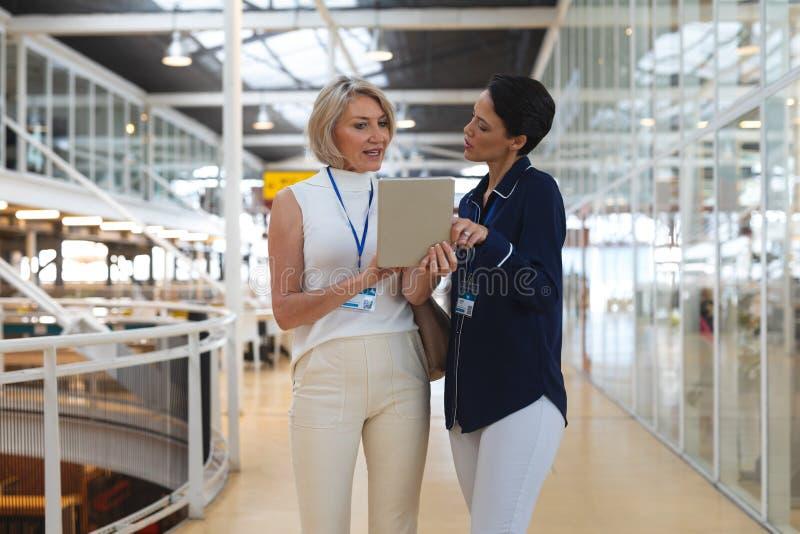 Affärskvinnor som diskuterar över den digitala minnestavlan i ett modernt kontor royaltyfria foton