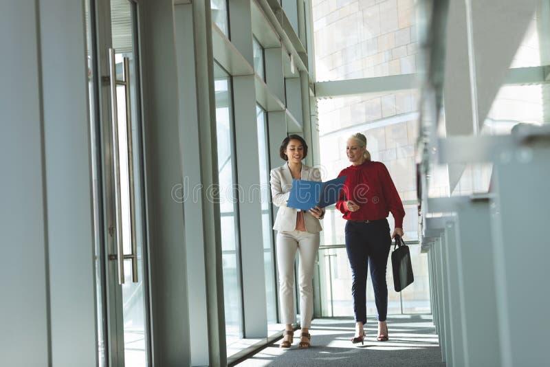 Affärskvinnor som diskuterar över dokument, medan gå i regeringsställning byggande arkivfoton