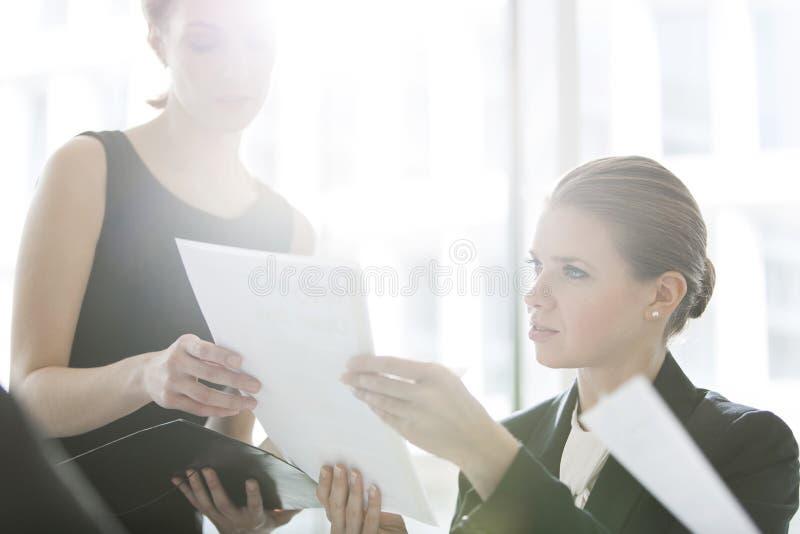 Affärskvinnor som i regeringsställning gör skrivbordsarbete fotografering för bildbyråer