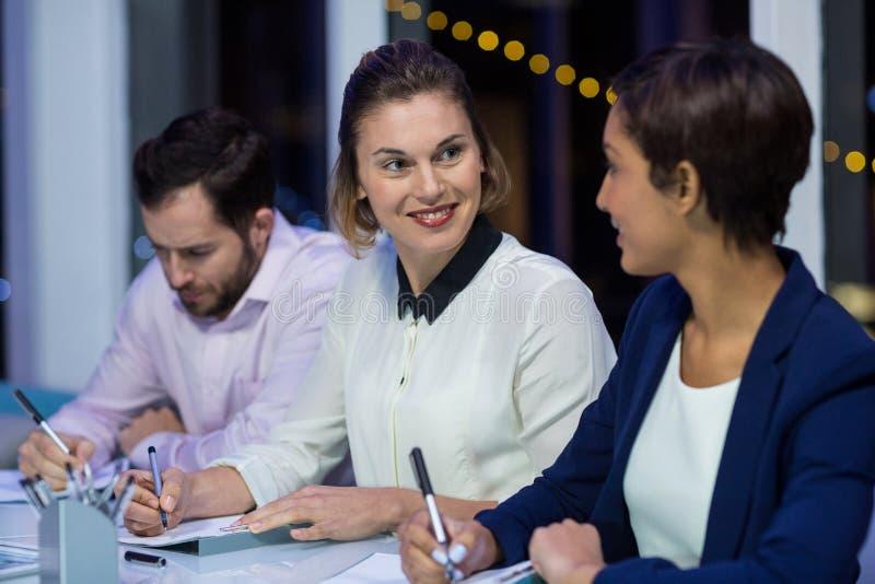 Affärskvinnor som i regeringsställning påverkar varandra med de royaltyfria foton