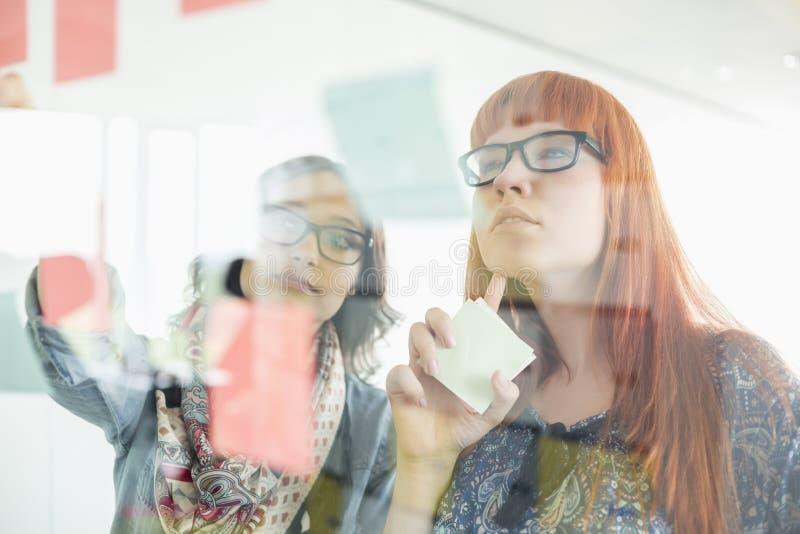 Affärskvinnor som läser klibbiga anmärkningar på glasväggen i idérikt kontor arkivbild