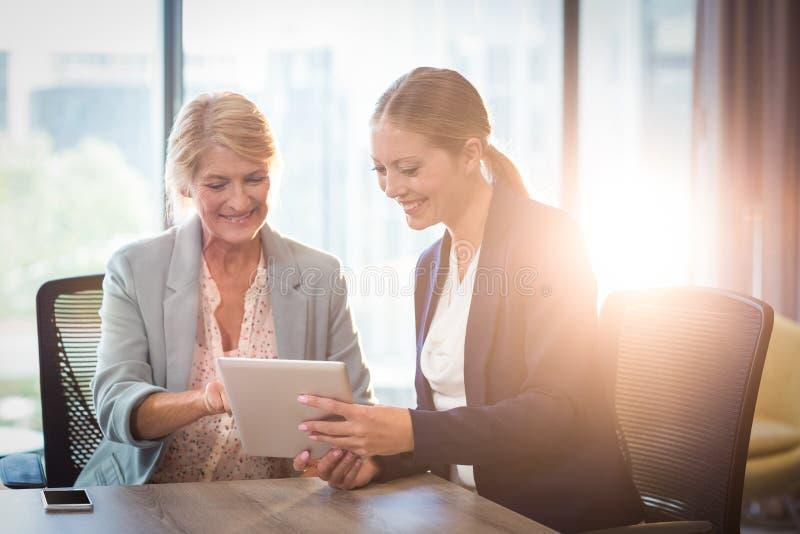 Affärskvinnor som påverkar varandra genom att använda den digitala minnestavlan royaltyfria foton