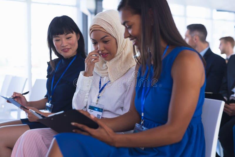 Affärskvinnor som påverkar varandra med de, medan delta i affärsseminarium royaltyfri foto