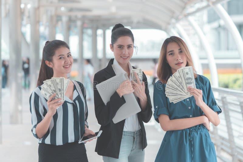 Affärskvinnor som in räknar pengarkassa deras hand royaltyfri bild