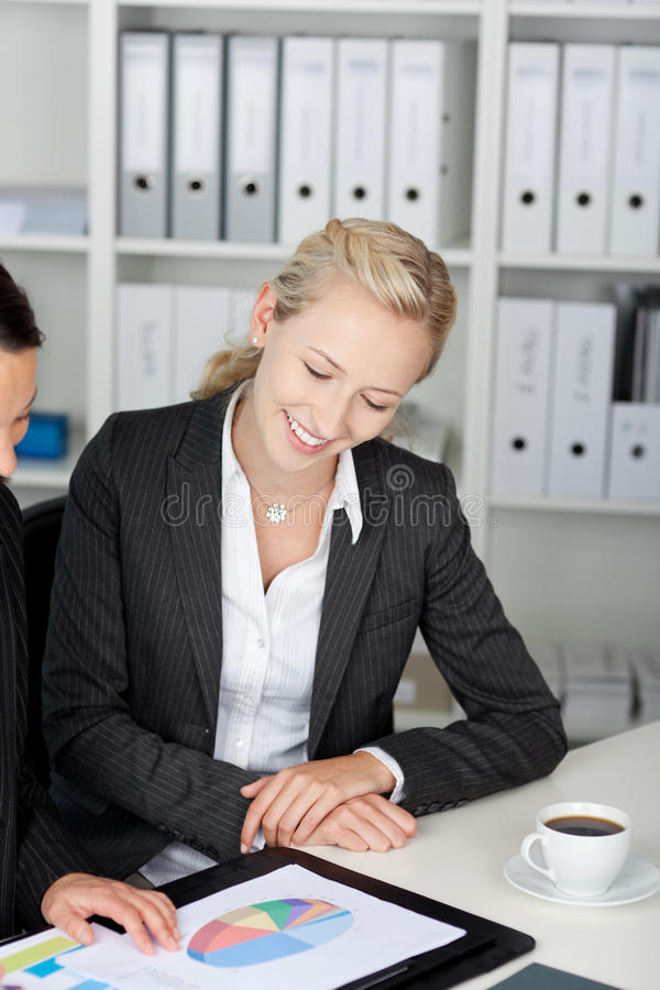 Affärskvinnor som ser pajdiagrammet på skrivbordet royaltyfri foto