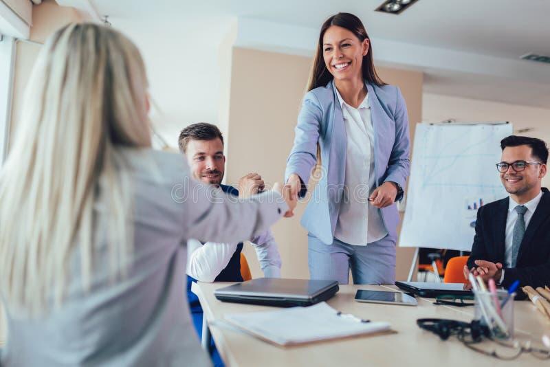 Affärskvinnor som skakar händer i mötesrum arkivfoto
