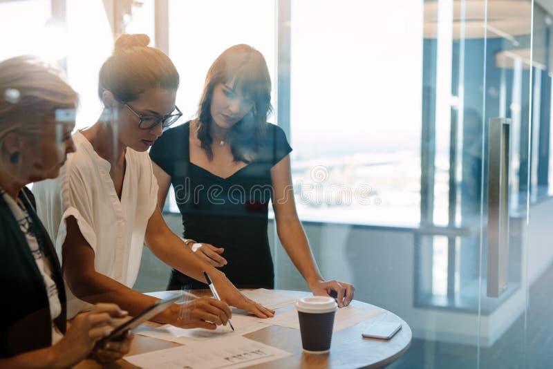 Affärskvinnor som står på tabellen och diskuterar ny strategie royaltyfria foton