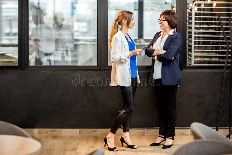 Affärskvinnor som talar i kontoret av bagerilagret arkivbild